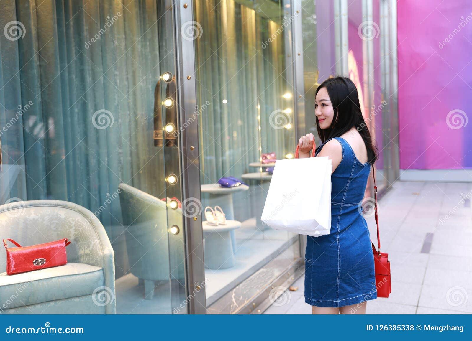 Счастливые покупки девушки женщины Азии китайские восточные восточные молодые ультрамодные в моле с сумками смотрят окно покупок