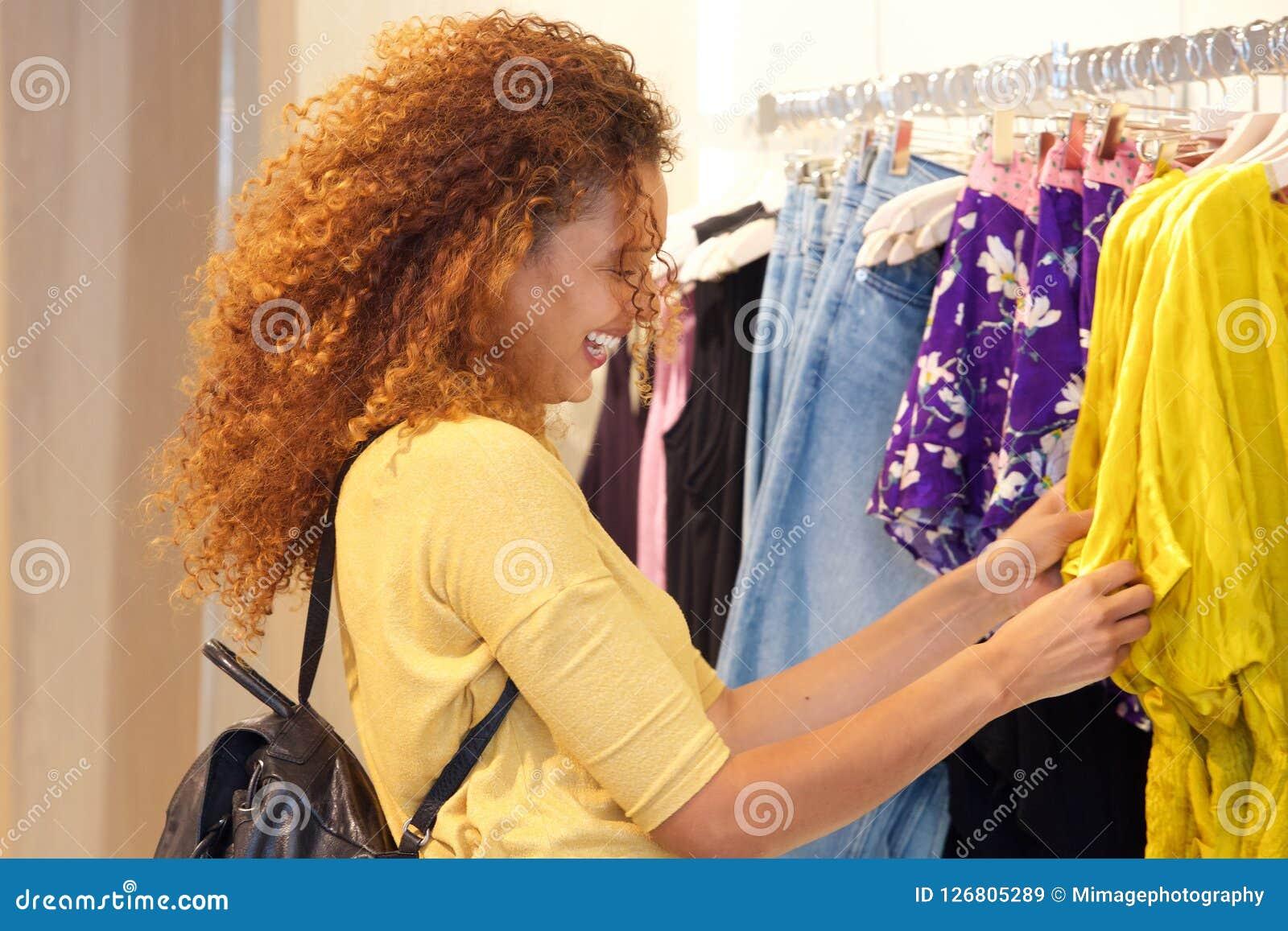 Счастливые покупки молодой женщины для одежд в магазине