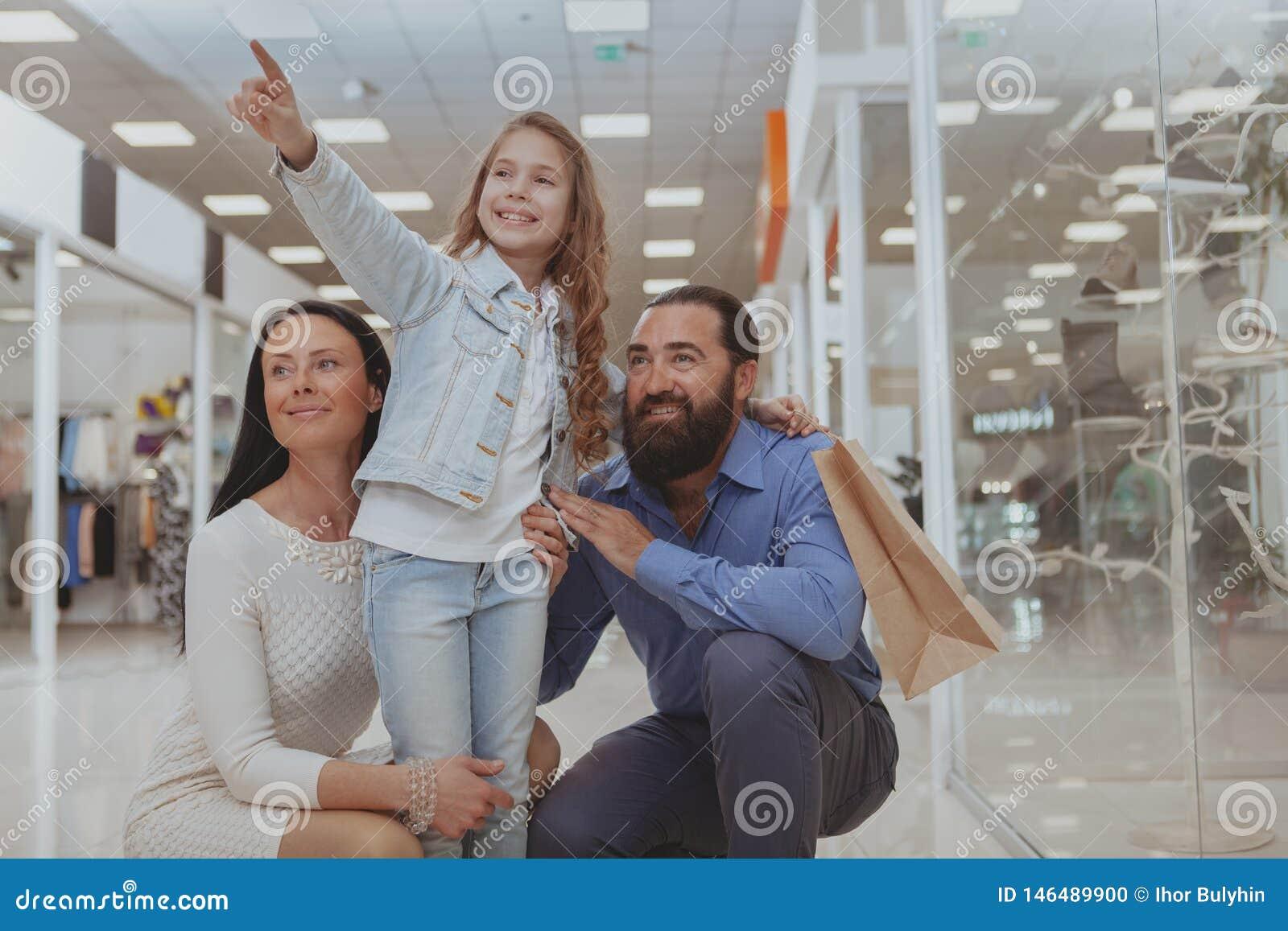 Счастливые покупки семьи на торговом центре совместно