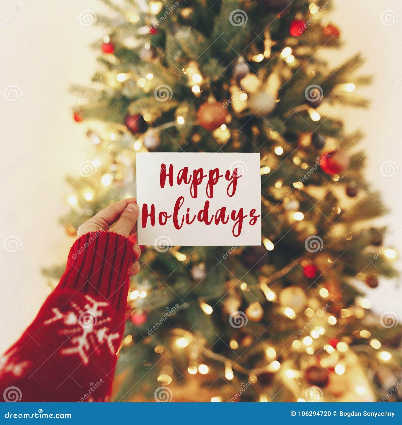Счастливые праздники отправляют СМС, приветствия сезонов, карточка руки на предпосылке