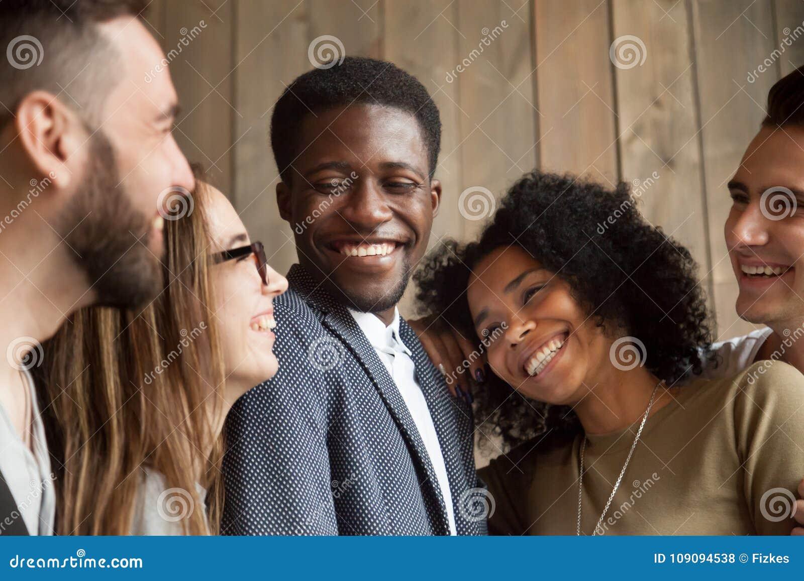 Счастливые разнообразные черно-белые люди собирают усмехаясь toget выпуска облигаций