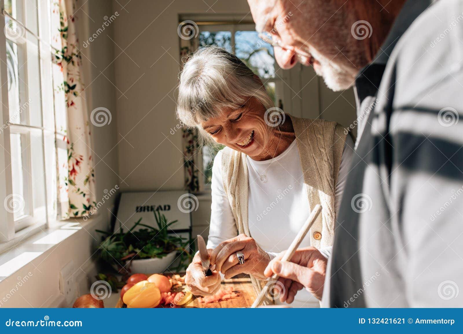 Счастливые старшие пары делая еду стоя в кухне