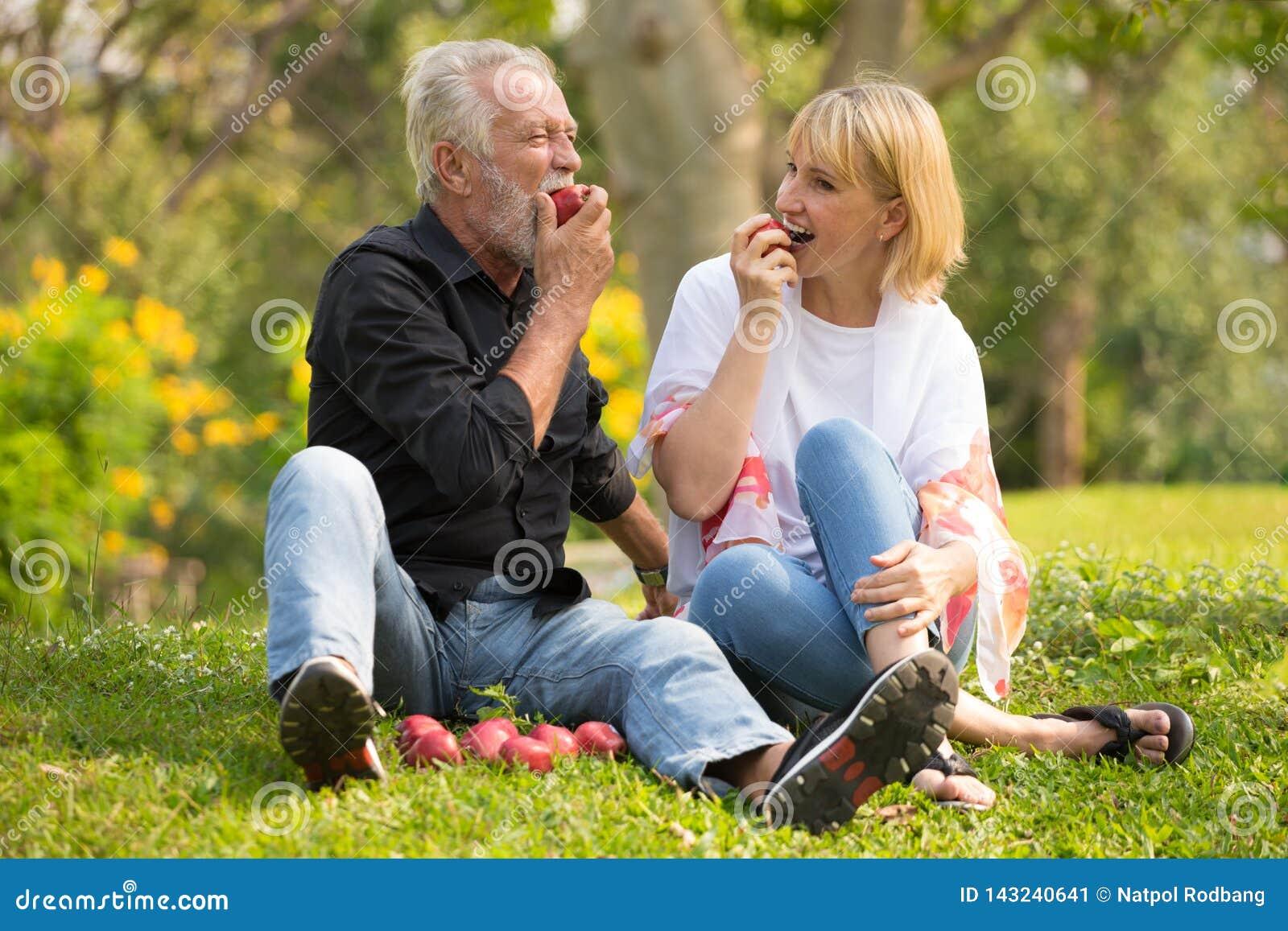 Счастливые старшие пары ослабляя в утреннем времени яблока еды парка совместно старые люди сидя на траве в парке осени пожило