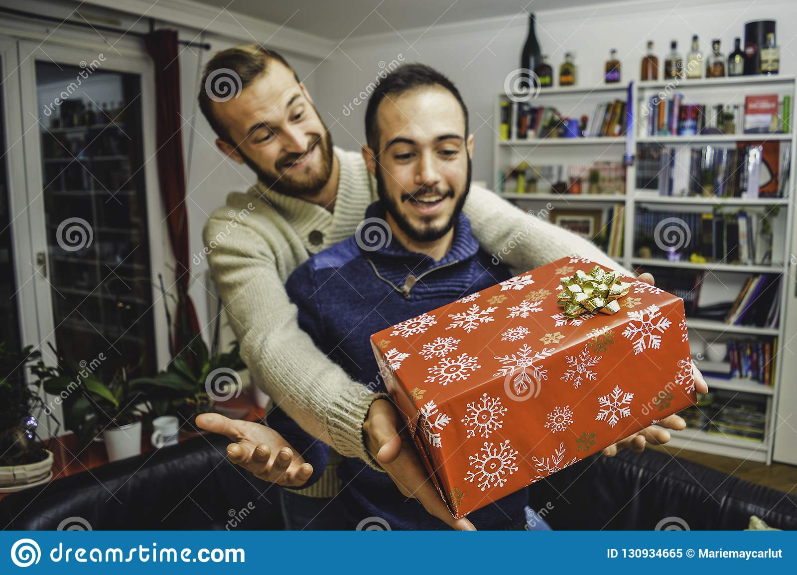 Счастливые удивленные молодые красивые пары гея празднуя и давая подарок дома