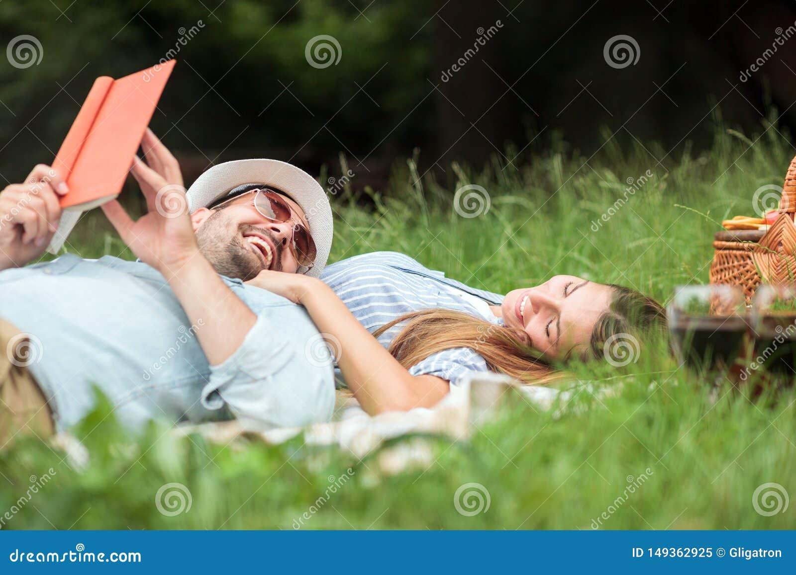 Счастливые усмехаясь молодые пары ослабляя в парке Лежать на одеяле пикника