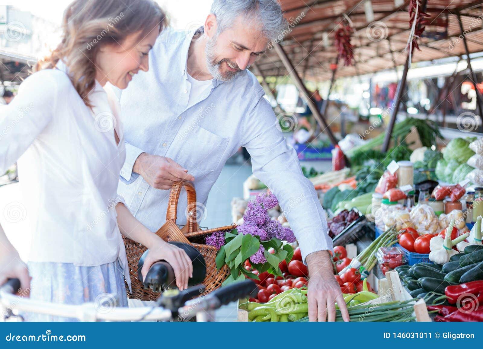 Счастливые усмехаясь покупки супруга и жены для бакалей и свежих продуктов в рынке