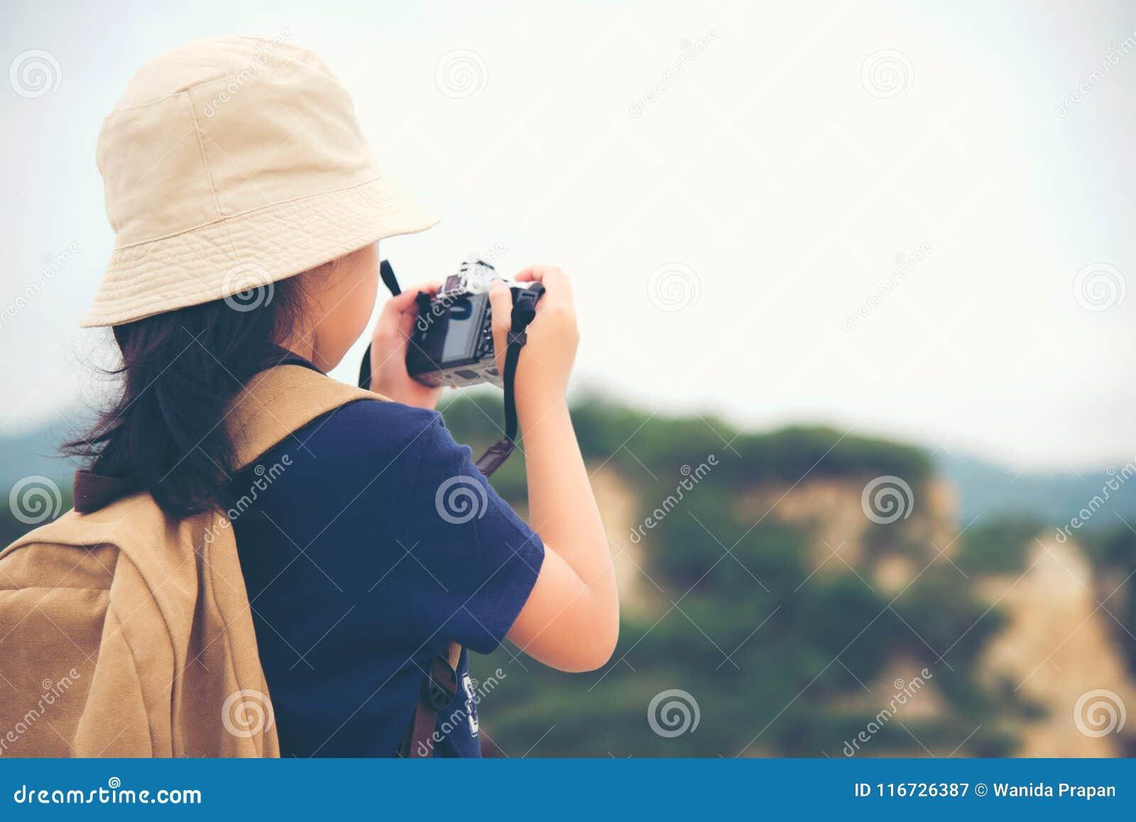 Счастливые усмехаясь рюкзак девушки кавказских детей азиатские и камера держать для принимают фото проверяют внутри на горе