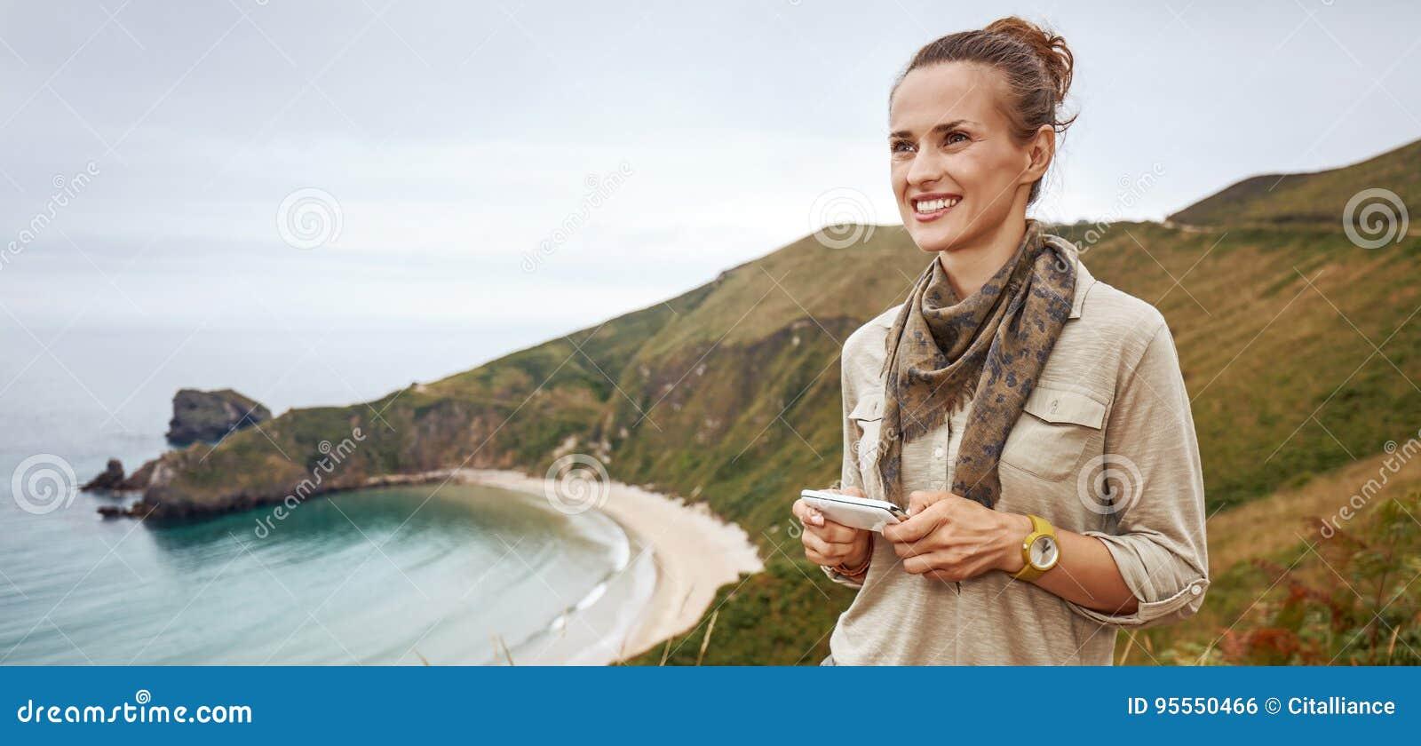 Счастливые sms сочинительства hiker женщины перед ландшафтом вида на океан