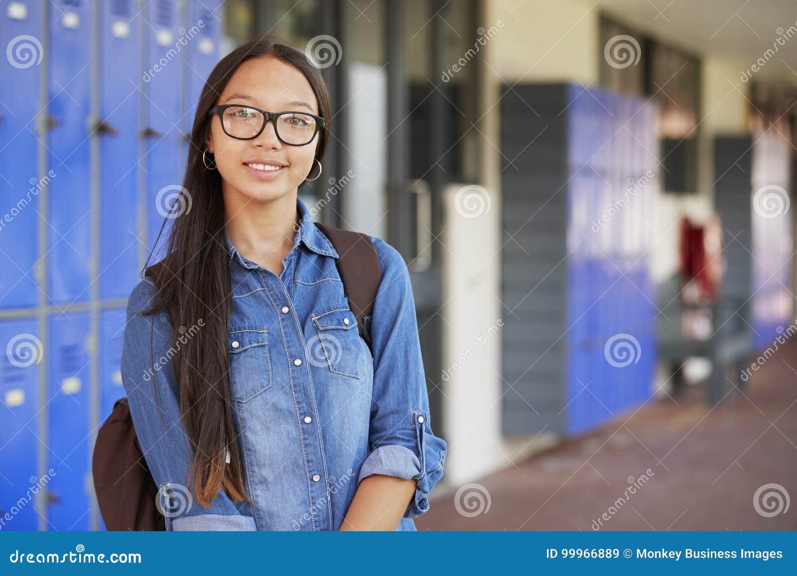 Счастливый азиатский девочка-подросток усмехаясь в коридоре средней школы