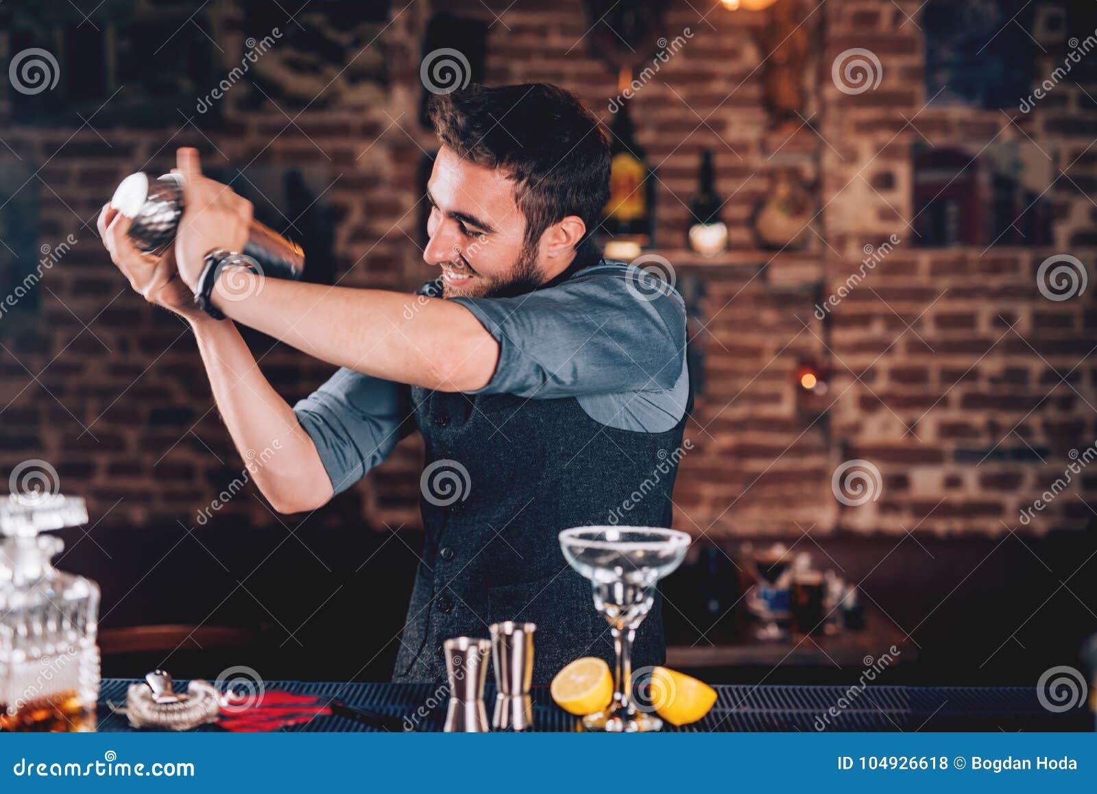 счастливый бармен используя шейкер для подготовки коктеиля Портрет бармена делая текила основал маргариту на местном пабе