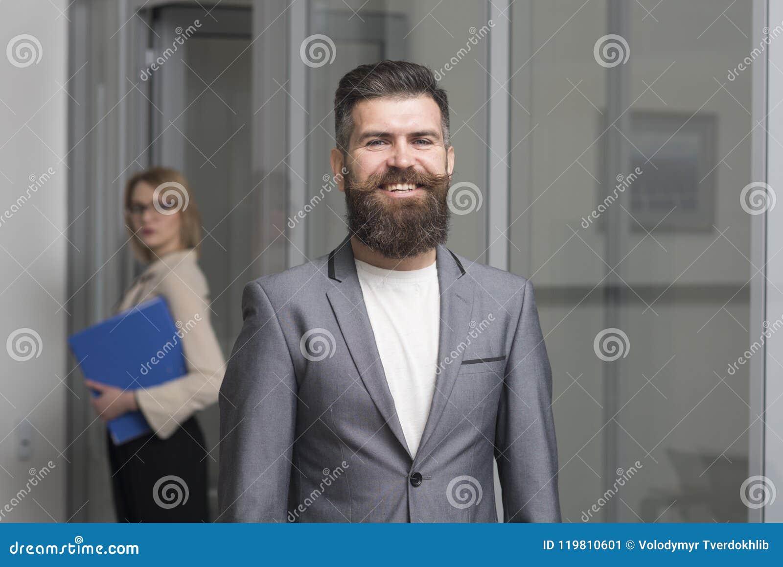 Счастливый бизнесмен с запачканной женщиной на предпосылке Бородатый человек в официально костюме в офисе Уверенно улыбка человек