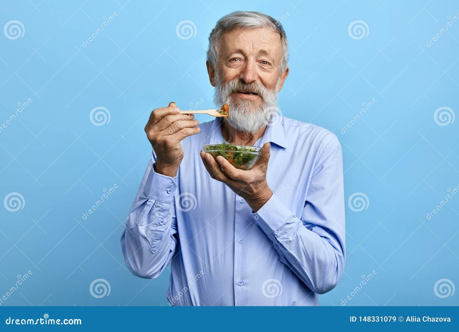 Счастливый бородатый человек есть салат, здравоохранение