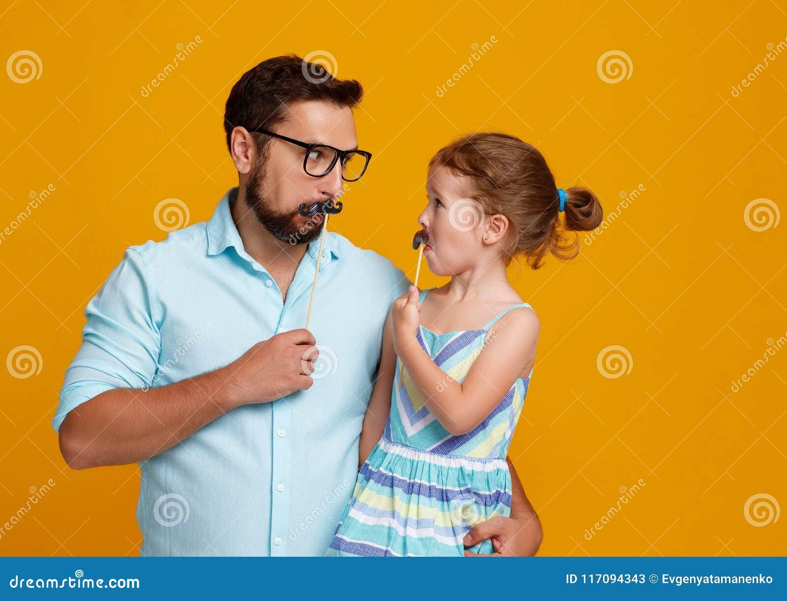 Счастливый день ` s отца! смешной папа и дочь с околпачивать усика