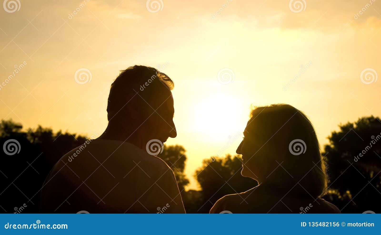 Счастливый достигший возраста супруг смотря один другого, романтичную дату на заходе солнца, нежные отношения