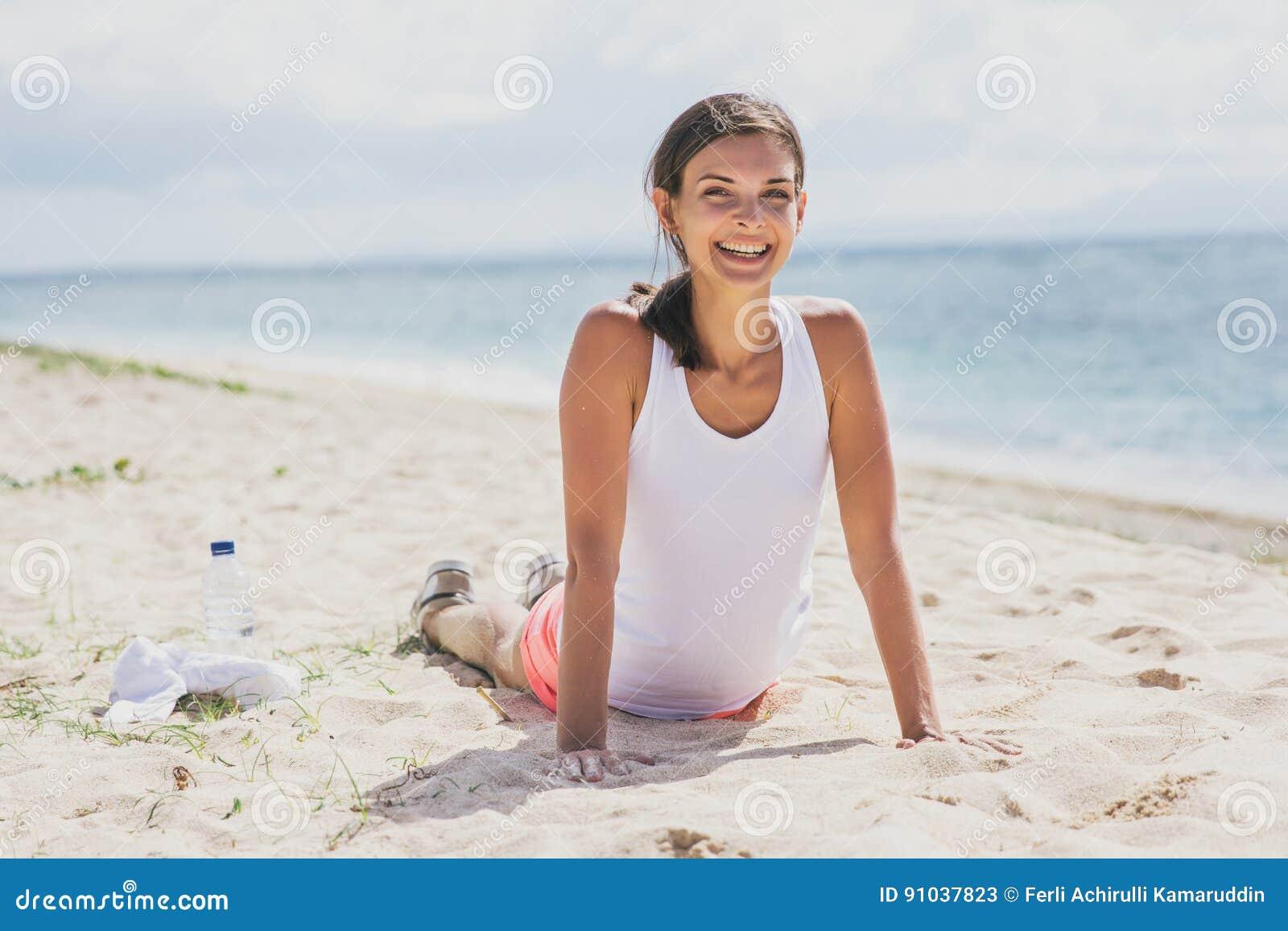 Счастливый здоровый делать женщины нажимает вверх на пляже