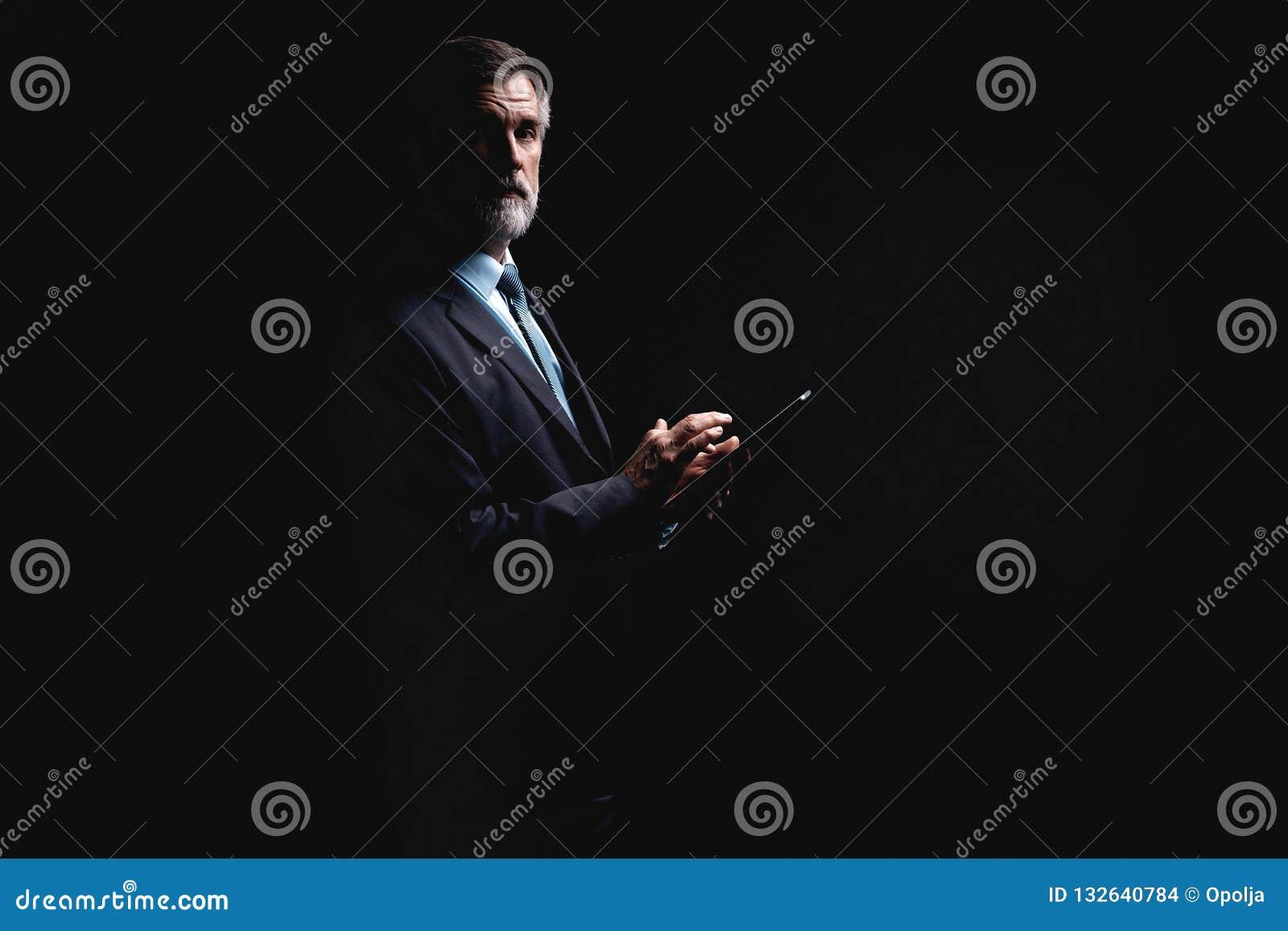 Счастливый зрелый бизнесмен работая с современным планшетом изолированным на черной предпосылке