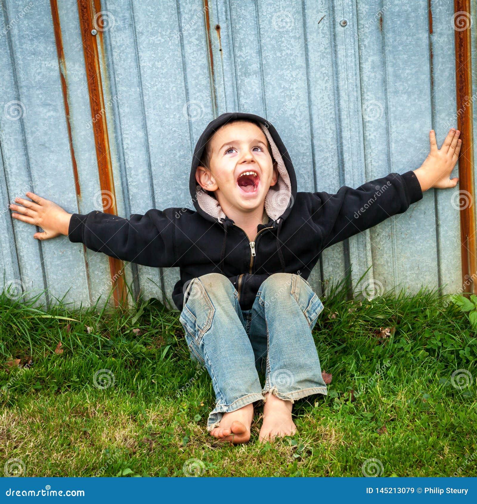 Счастливый крича бездомный мальчик