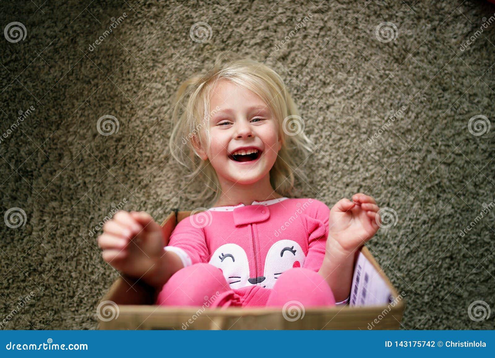 Счастливый маленький ребенок смеясь по мере того как она играет в картонной коробке на ее доме