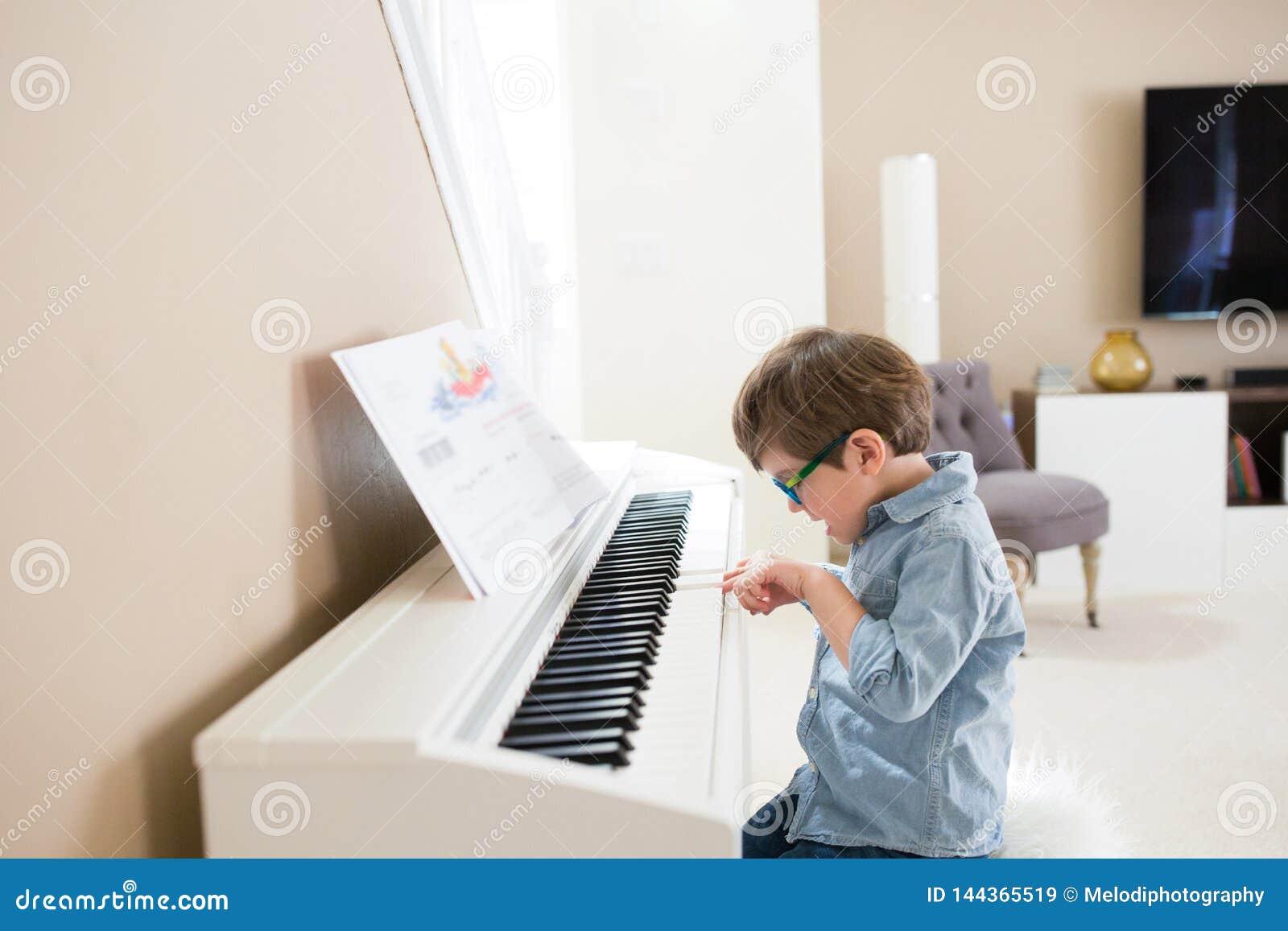 Счастливый малыш играя рояль