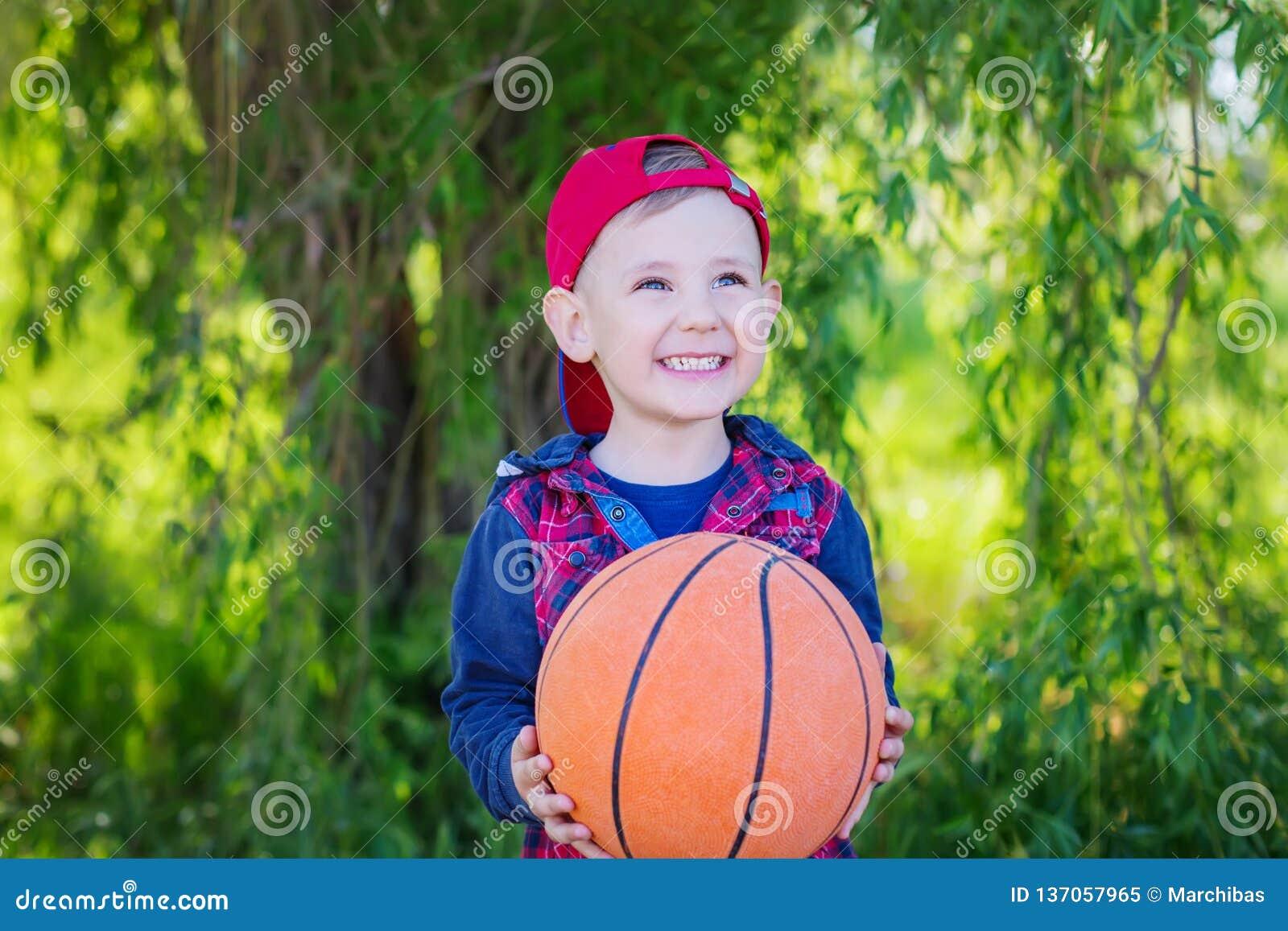 Счастливый мальчик вручая баскетбол,