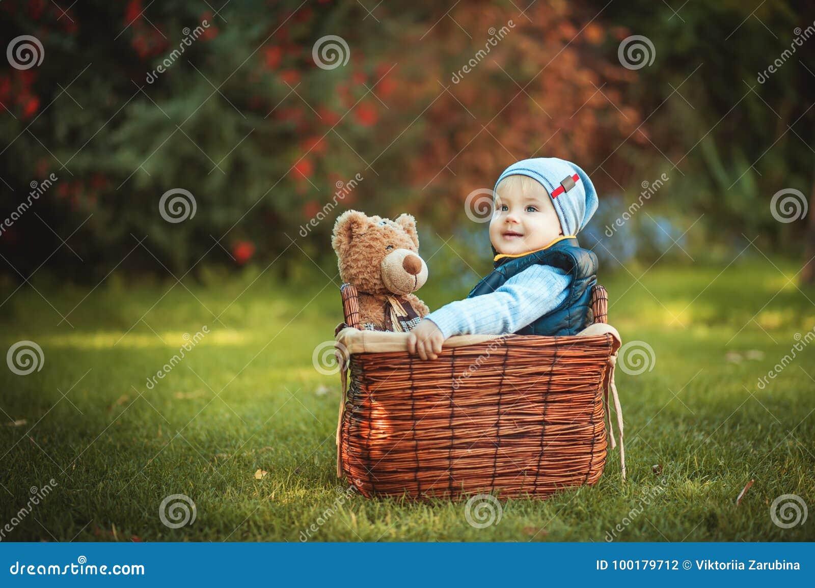 Счастливый мальчик маленького ребенка играя с игрушкой медведя пока сидящ в корзине на зеленой лужайке осени Дети наслаждаясь дея