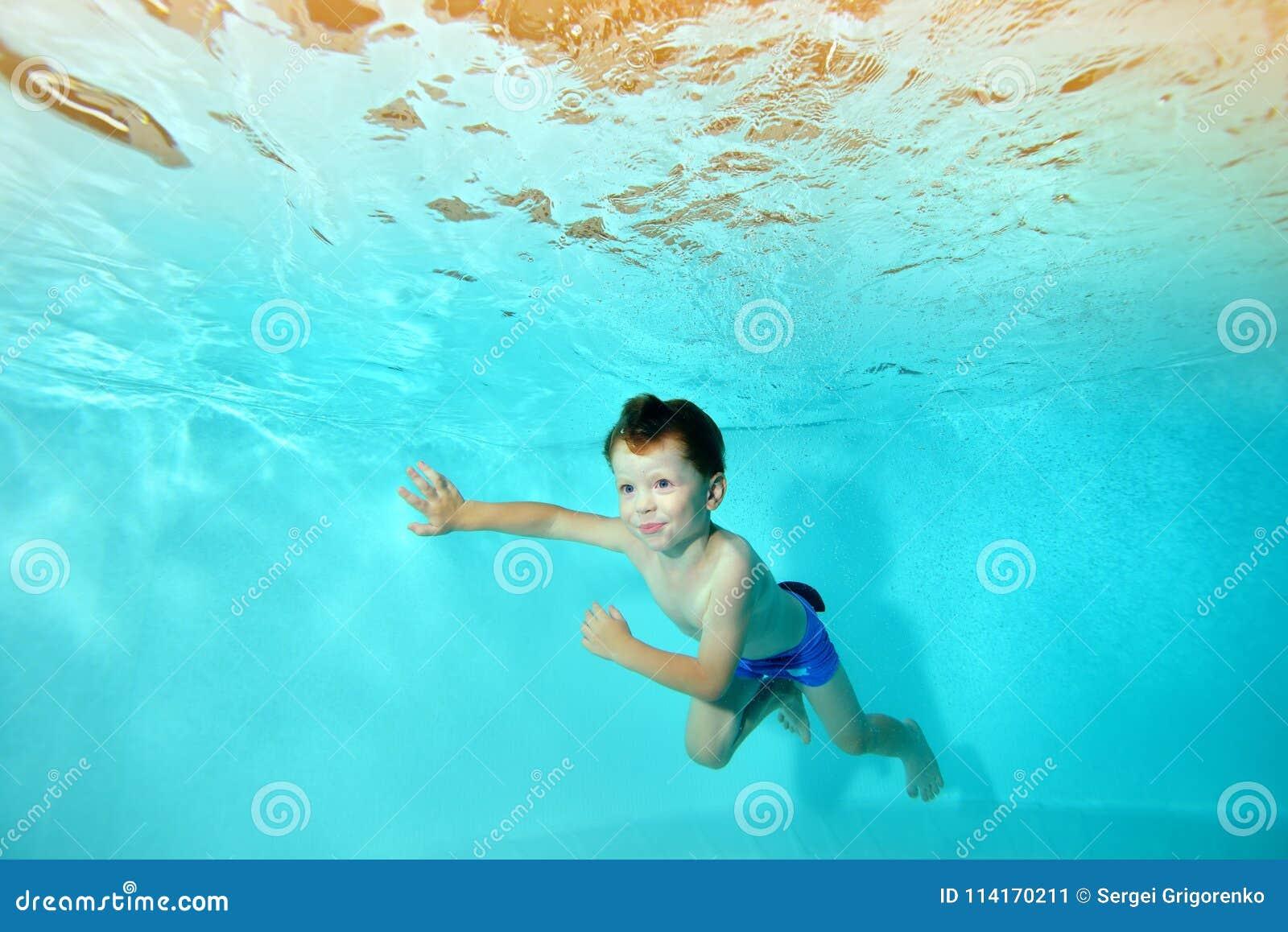 Счастливый мальчик плавает под водой в бассейне против фона ярких светов, смотря отсутствующим и усмехаться