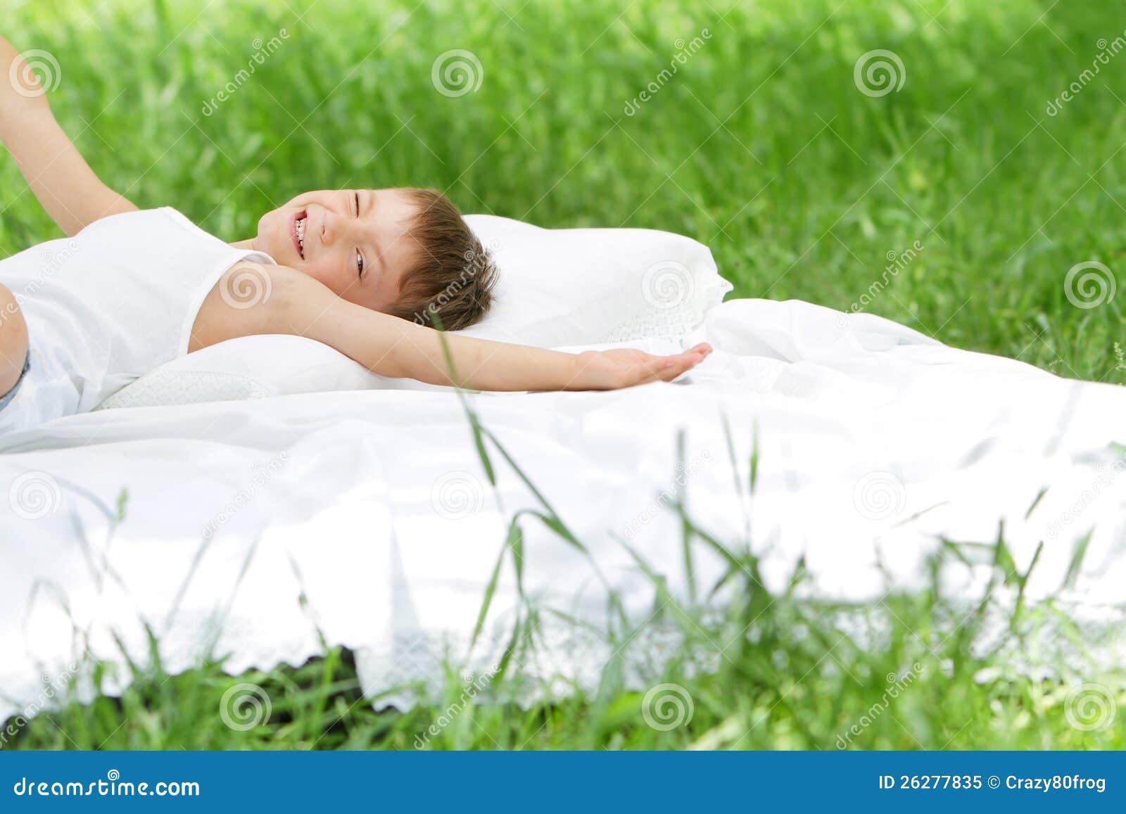 Счастливый мальчик ребенка ослабляя на природе