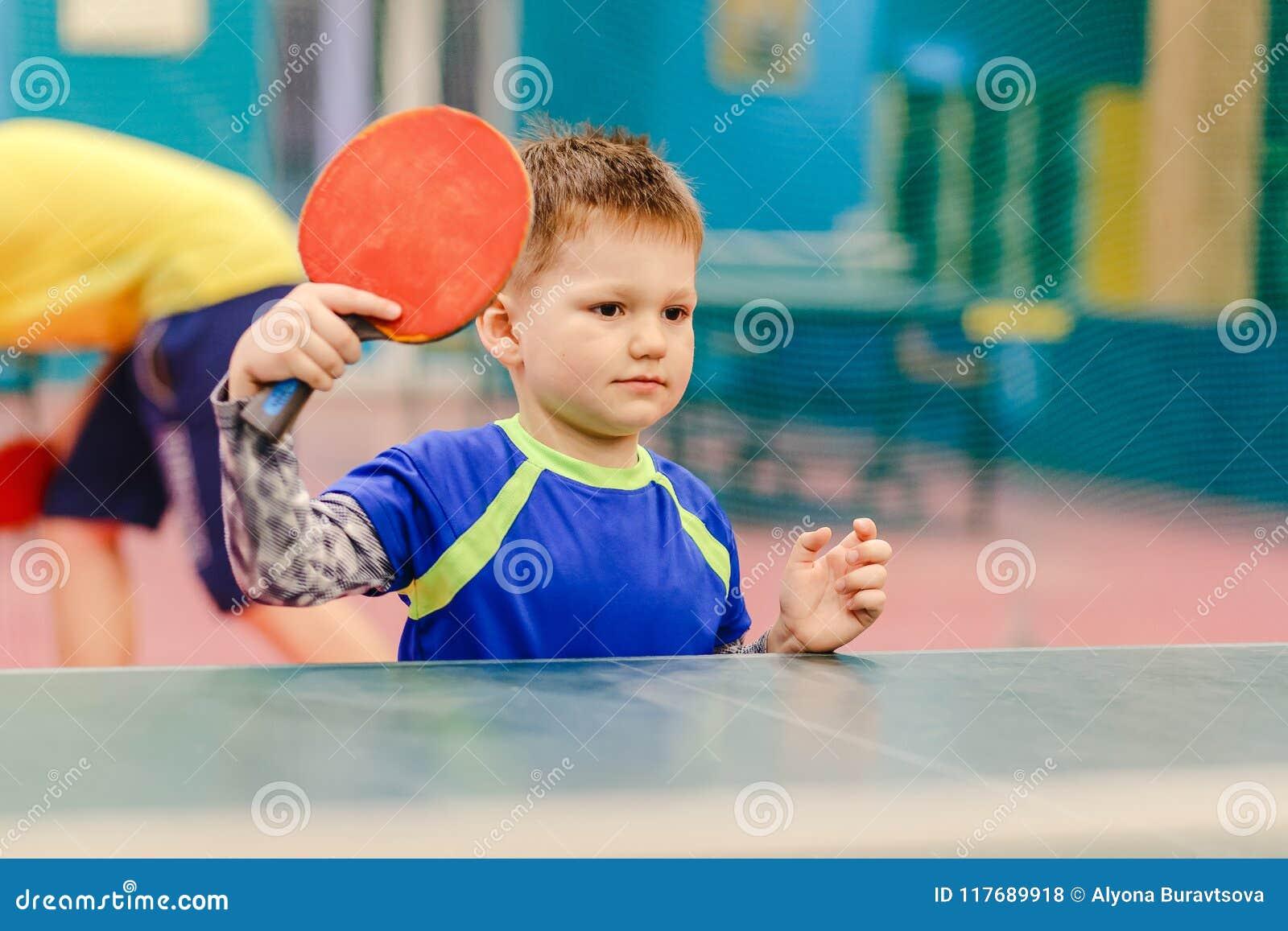 Счастливый мальчик стоя в зале тенниса, зала тенниса, ракетка тенниса, настольный теннис