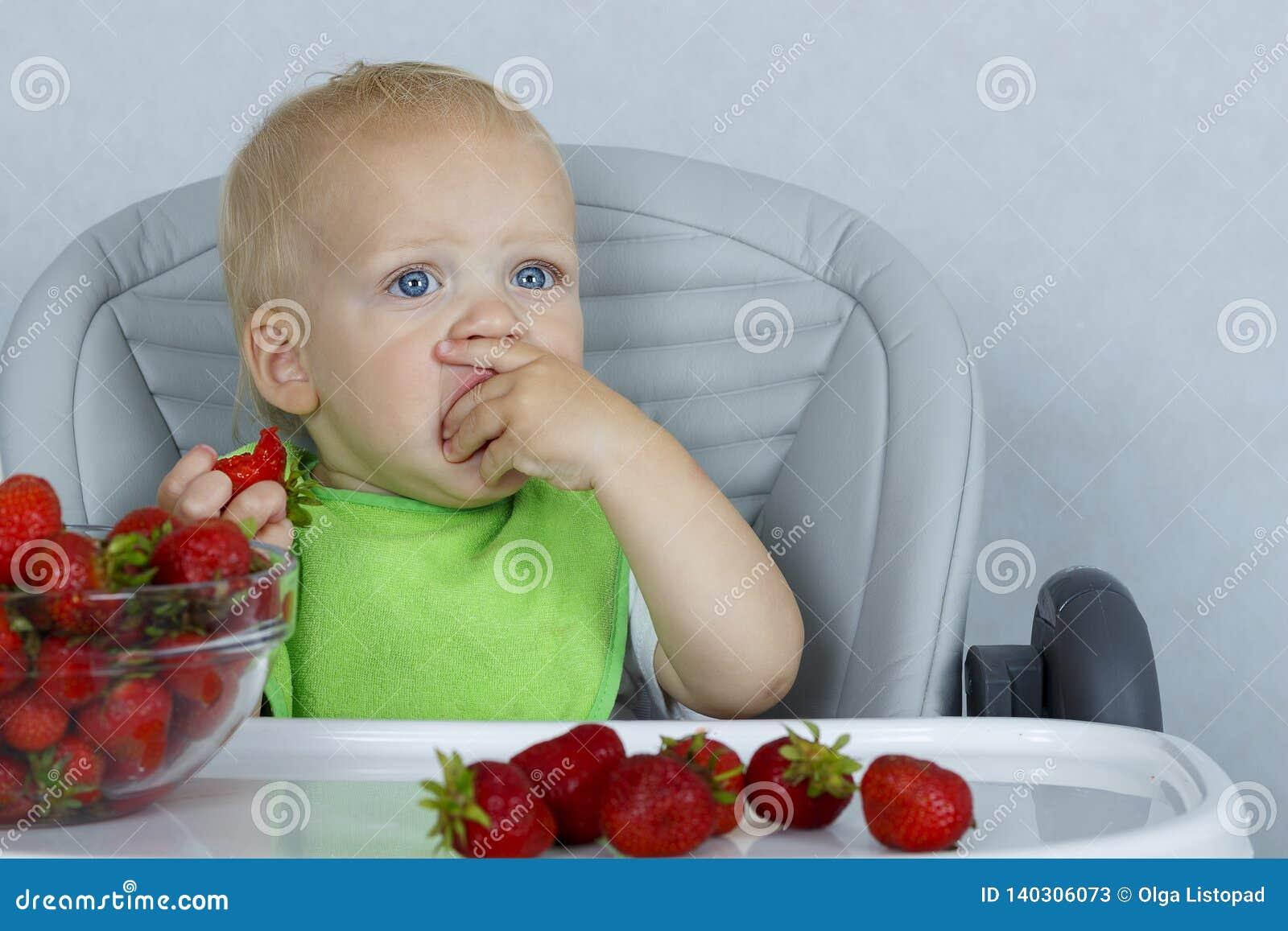 Счастливый мальчик с клубниками в стуле младенца, милый малыш есть зрелые плоды