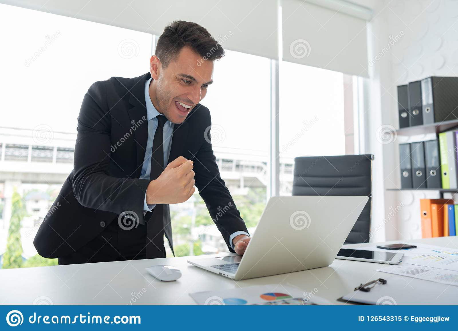 Счастливый молодой бизнесмен стоящ и смотрящ компьтер-книжка