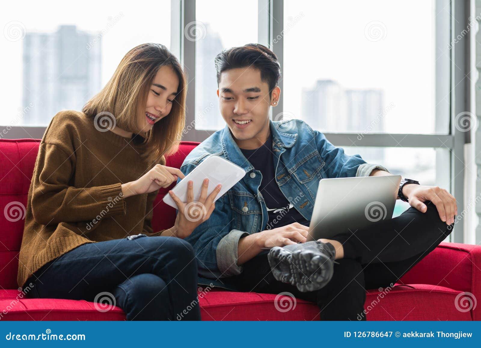 Счастливый молодой дизайнер пар используя цифровое toge планшета и ноутбука