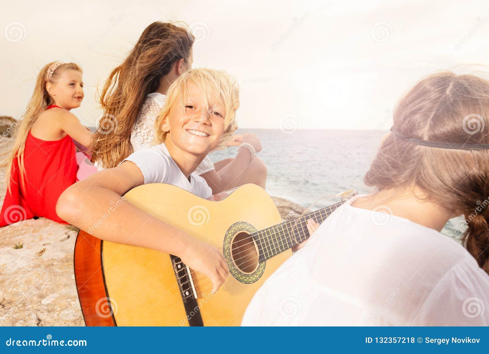 Счастливый подросток играя гитару на пляже