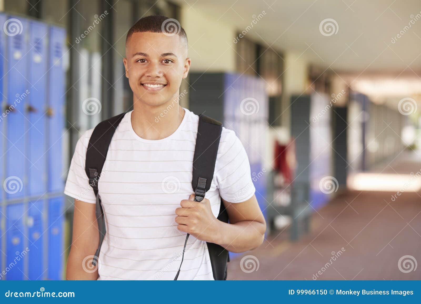 Счастливый подросток смешанной гонки усмехаясь в коридоре средней школы