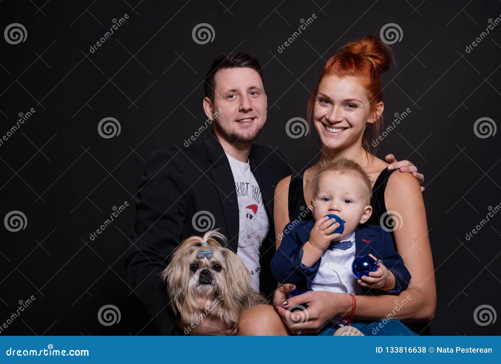 Счастливый портрет семьи с мальчиком и собакой в студии на Новый Год
