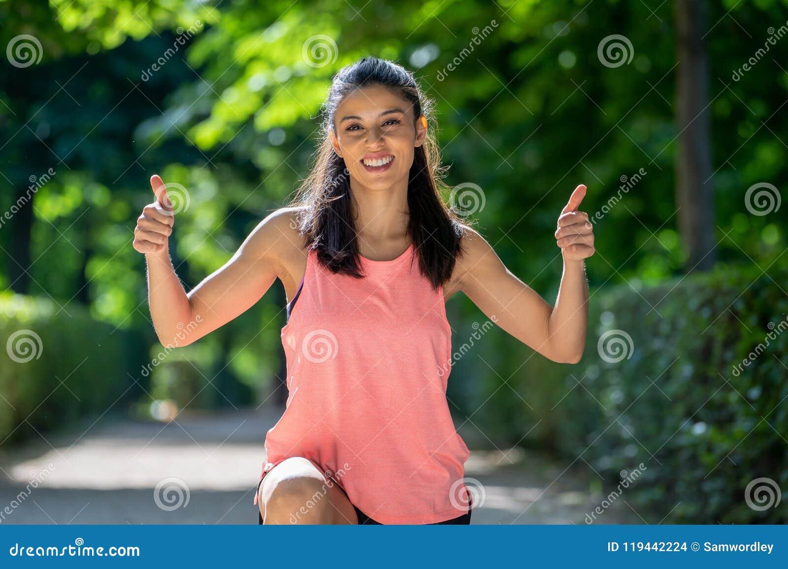 Счастливый портрет sportive девушки усмехаясь на камере с ее большими пальцами руки вверх