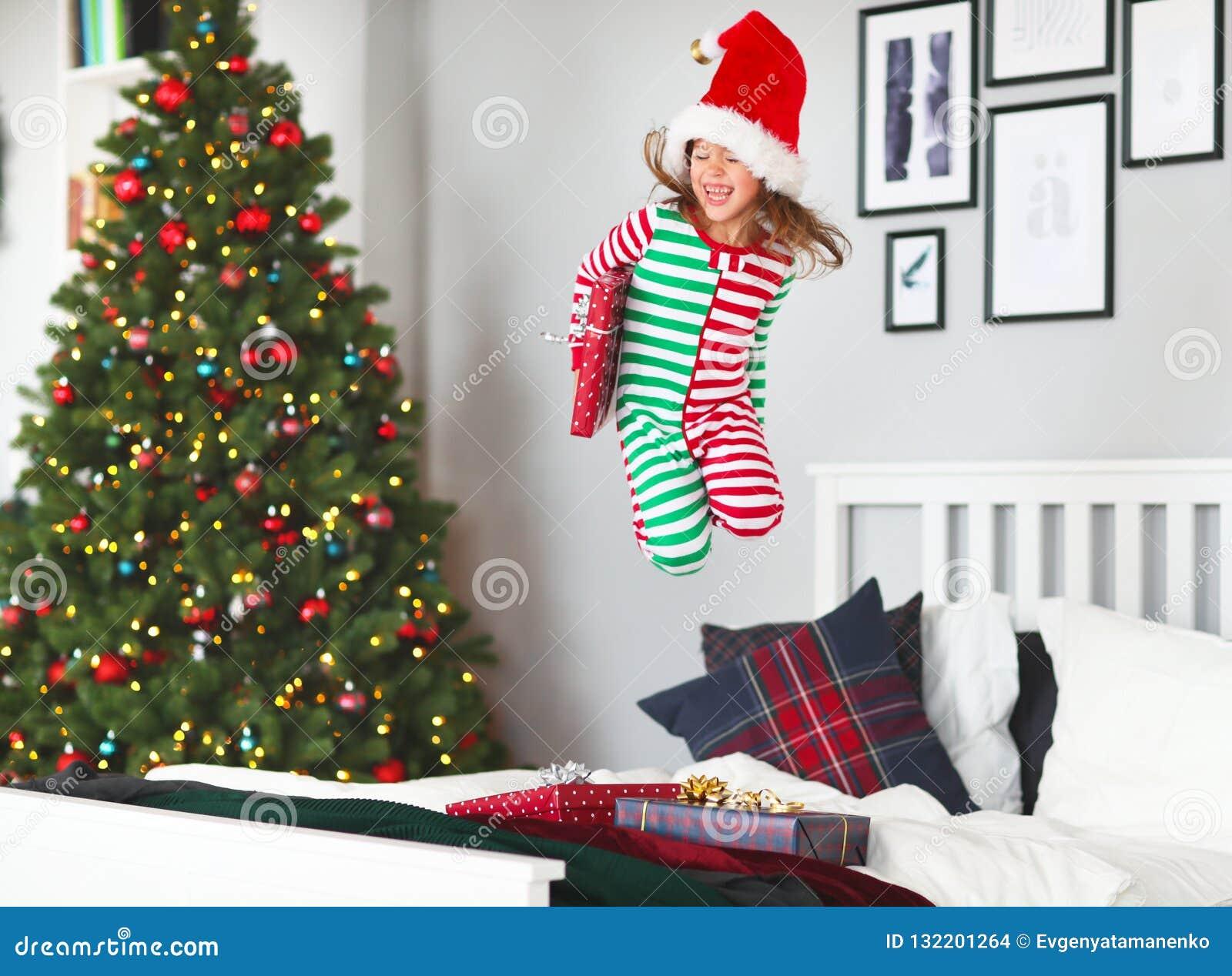 Счастливый ребенок в пижамах с подарками скача в кровать на рождестве m
