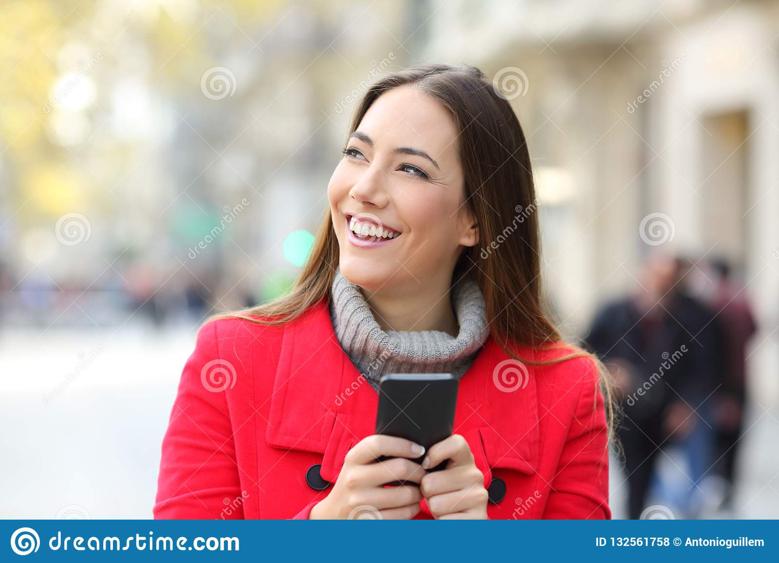 Счастливый телефон удерживания женщины смотря сторону в зиме
