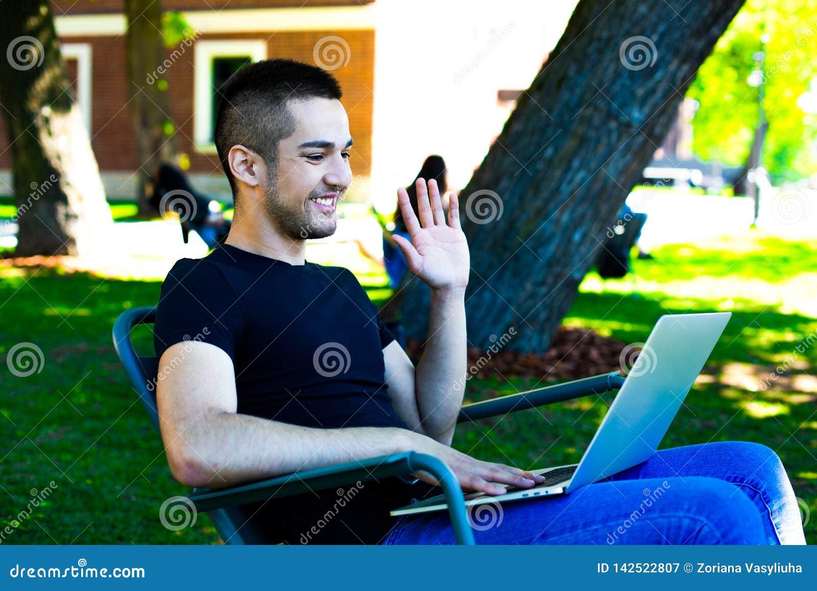Счастливый фрилансер человека имея конференцию веб-камеры через прибор тетради