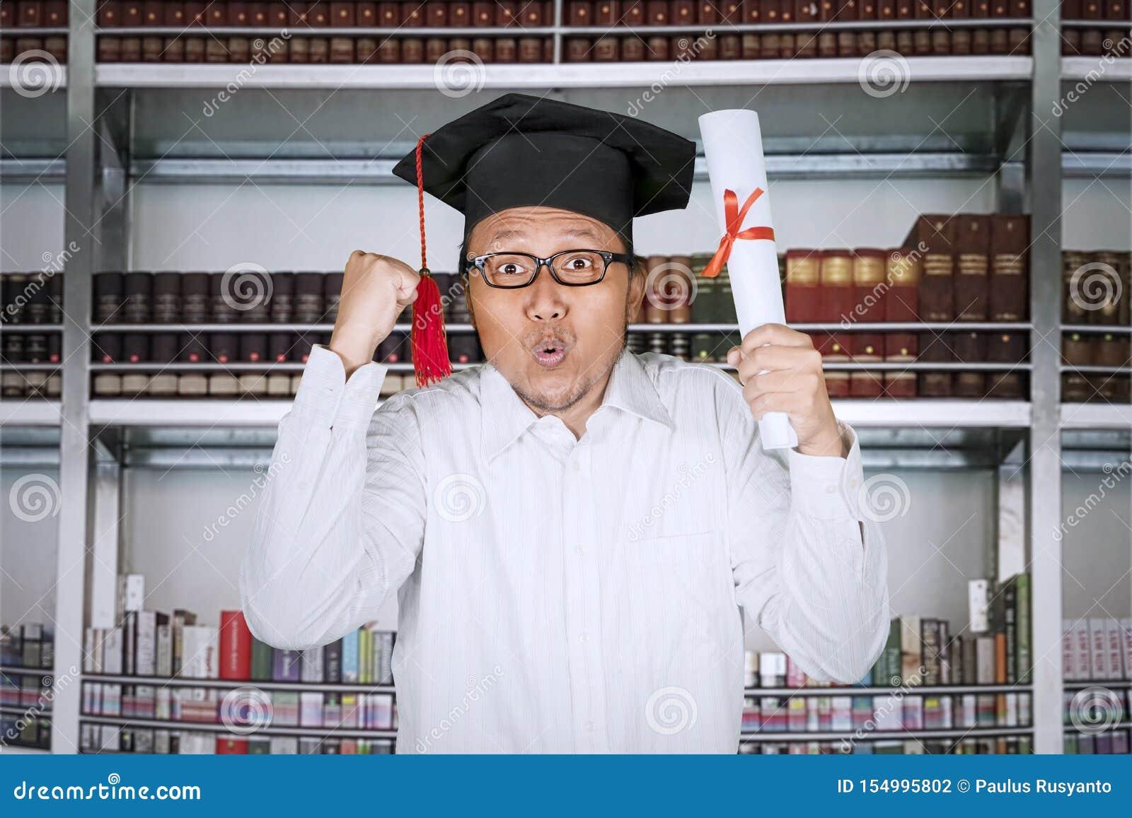 Счастливый человек поднимая руки и диплом