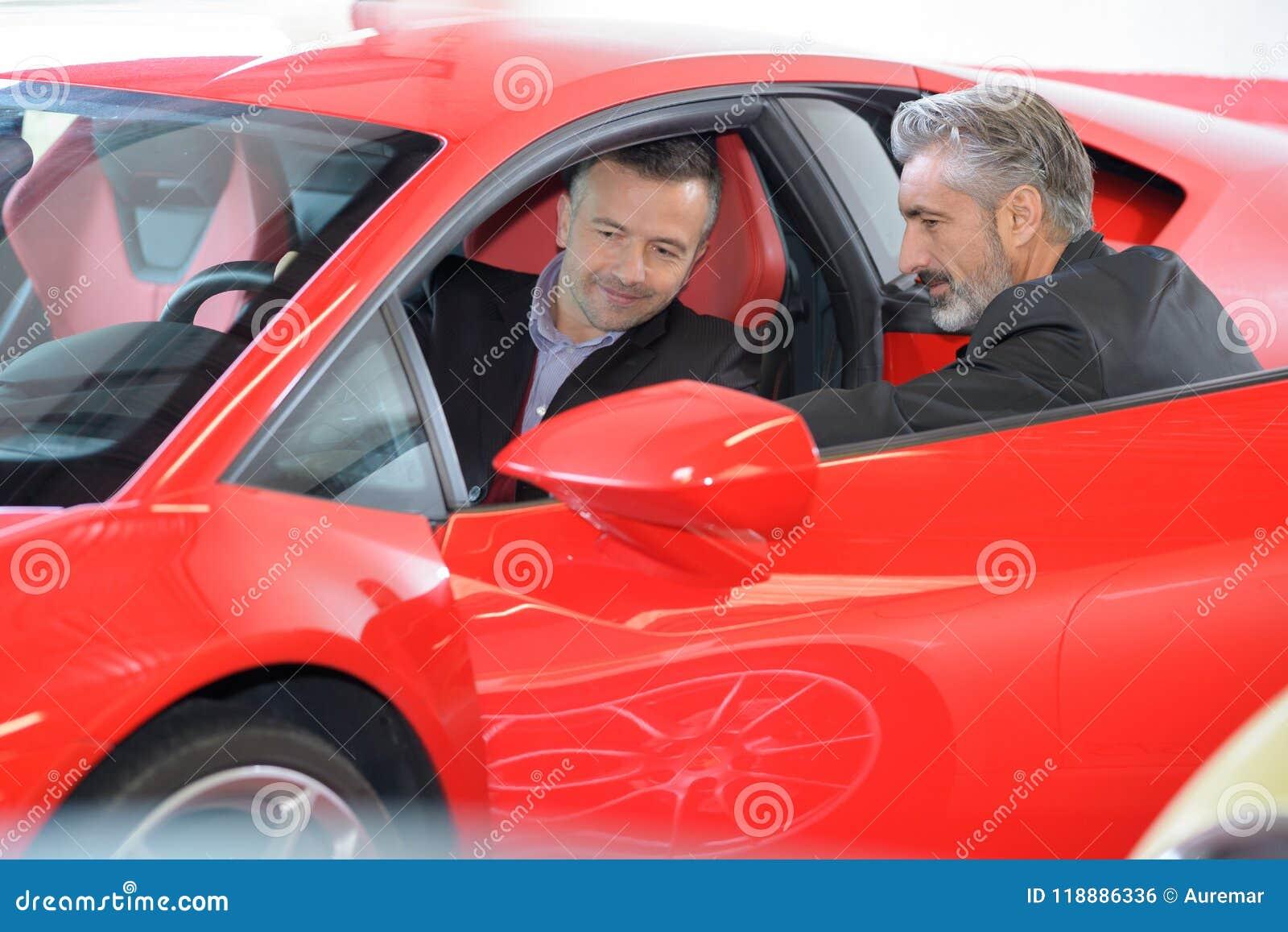 Счастливый человек с автодилером в автосалоне или салоне