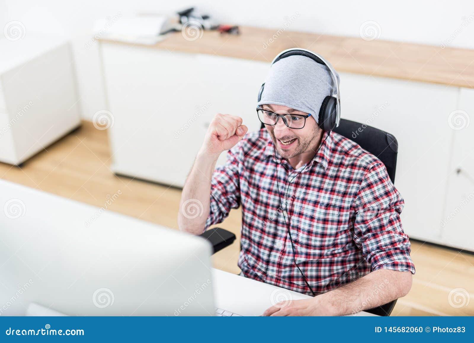 Счастливый gamer на его настольном компьютере