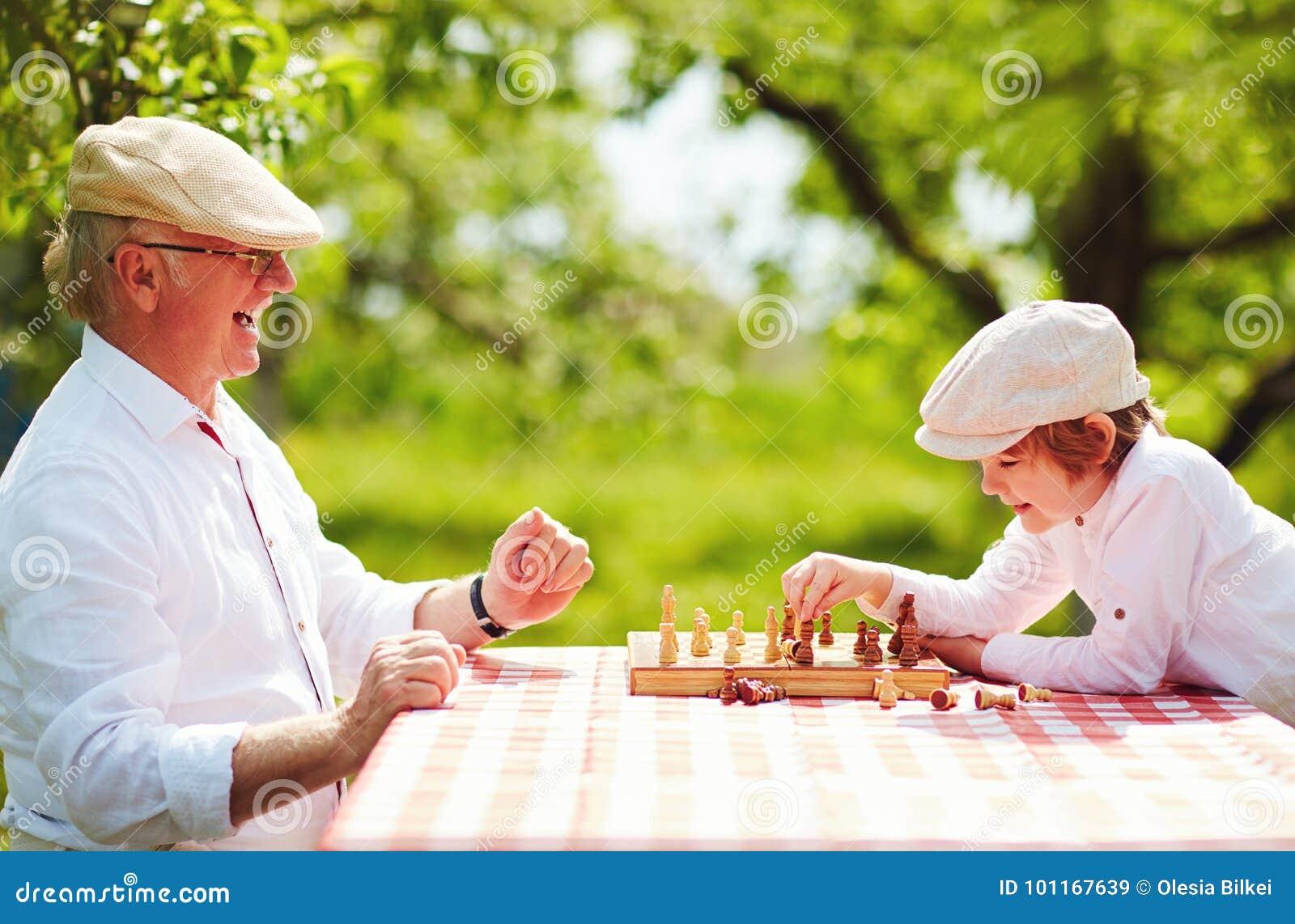 Счастливый grandpa и внук играя шахмат весной садовничают
