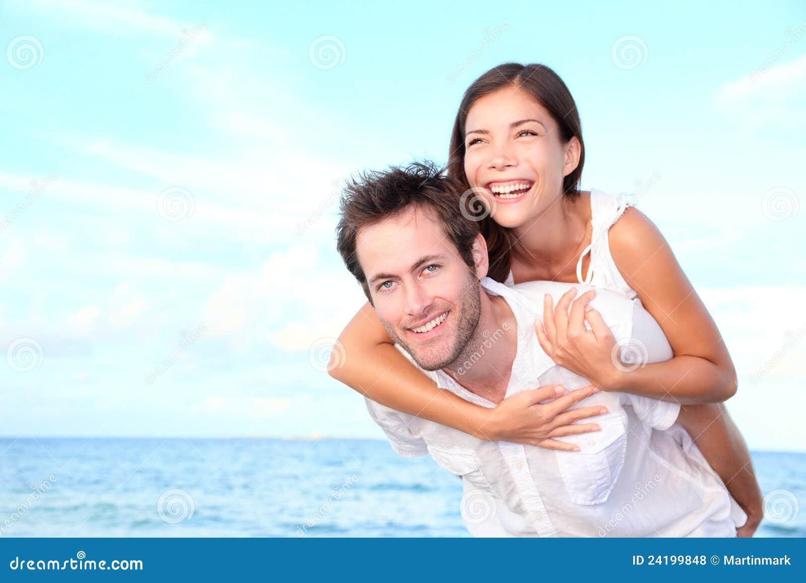Счастливый piggyback пар пляжа