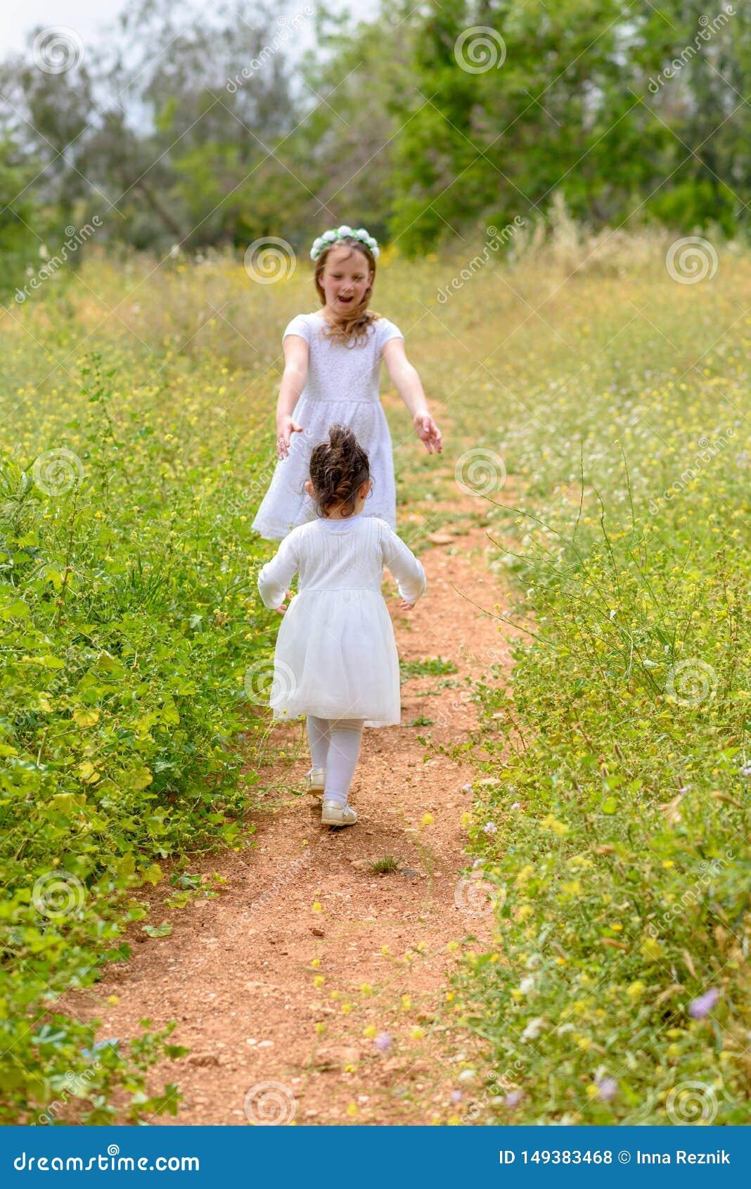 2 счастливых девушки играя ход на зеленом луге на открытом воздухе