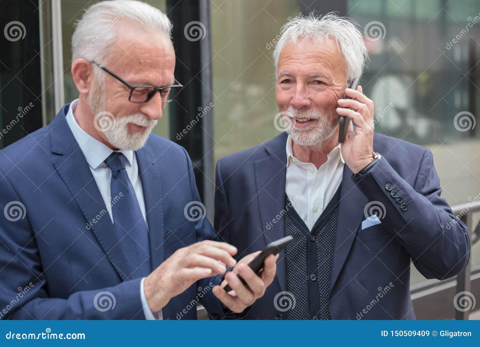 2 счастливых старших бизнесмена звоня телефонные звонки, стоя на тротуаре