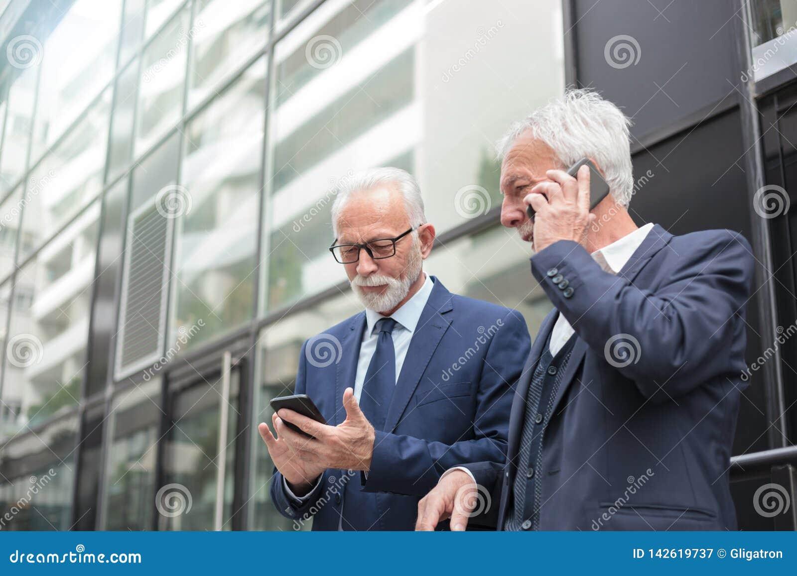 2 счастливых старших бизнесмена используя умные телефоны, говорить и послание
