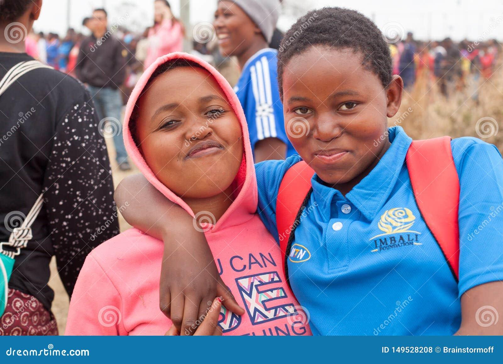 2 счастливых усмехаясь маленькой девочки африканца красивых обнимают outdoors на людях празднуя конец предпосылки обряда Umhlanga