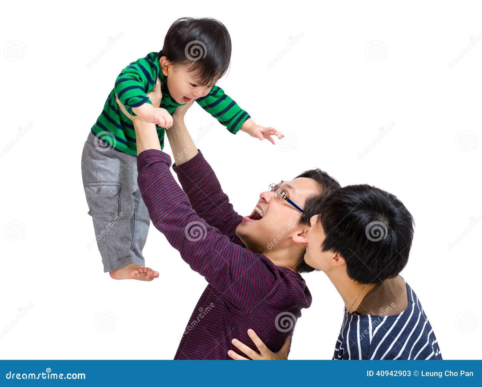 Счастливая азиатская семья при папа бросая вверх