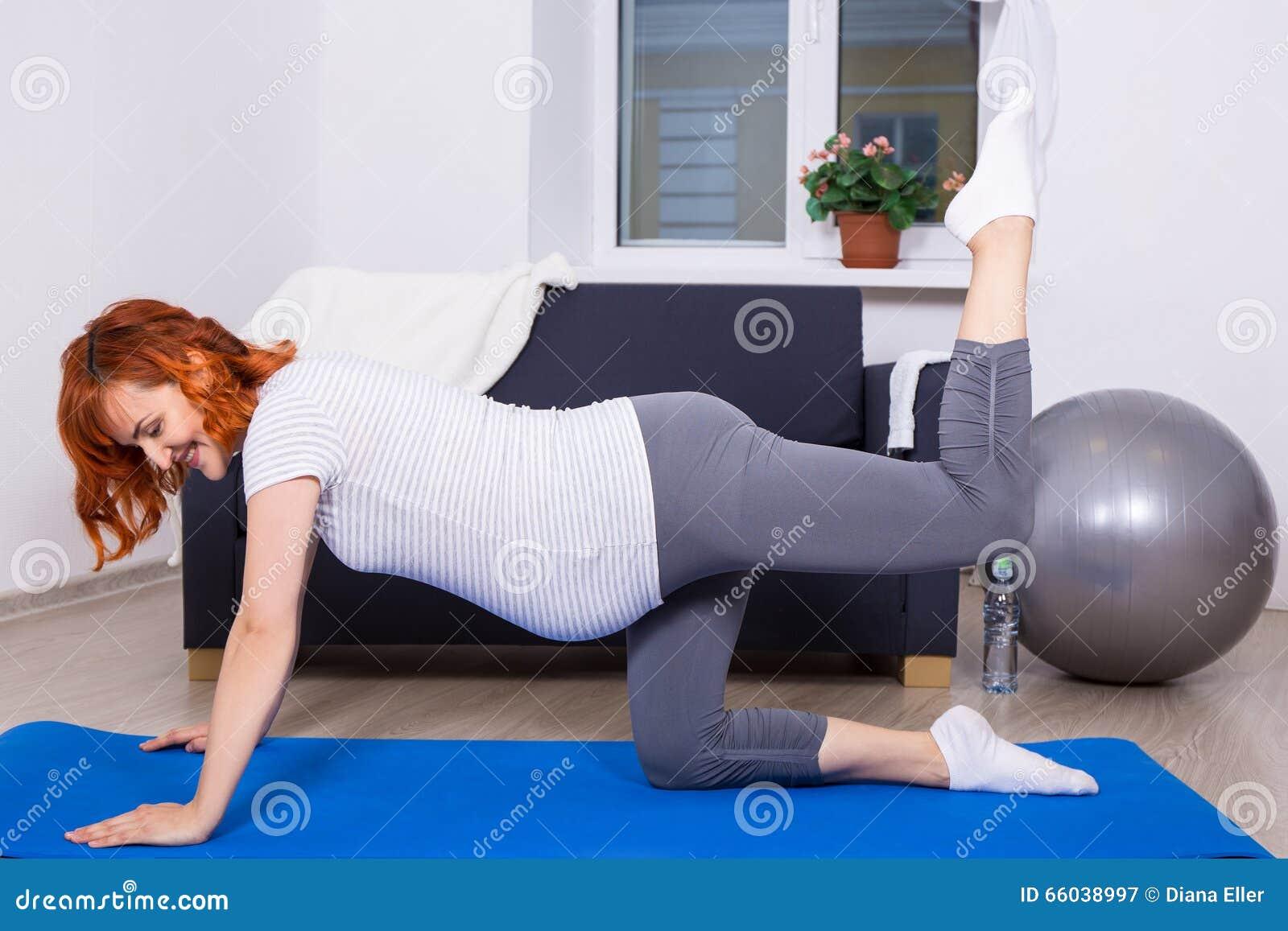 Счастливая беременная женщина делая протягивать работает в живущей комнате