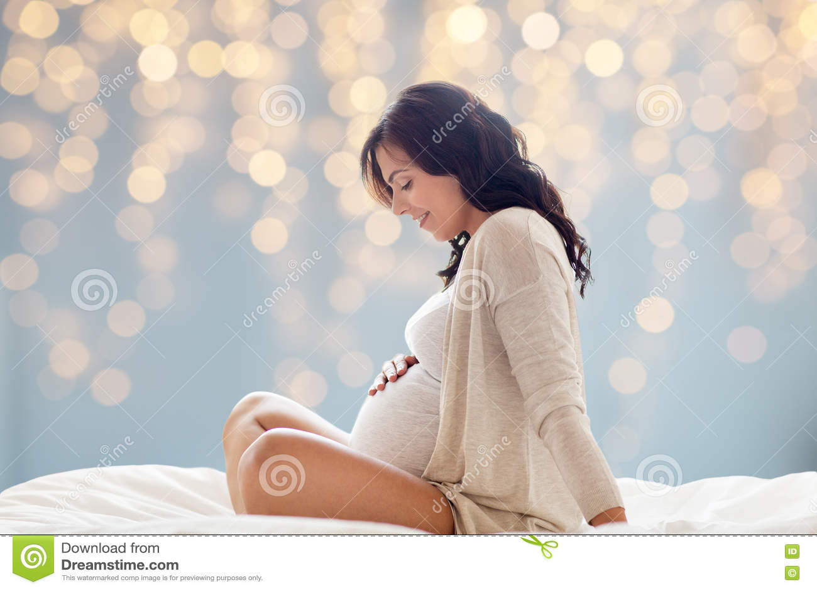 Счастливая беременная женщина сидя на кровати